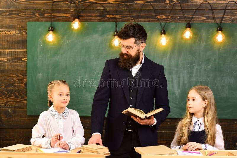 Rodzice zazwyczaj stawiają ich dzieciaków w akademickiego trenowanie Baczni ucznie pisze coś w ich nutowych ochraniaczach podczas zdjęcie royalty free