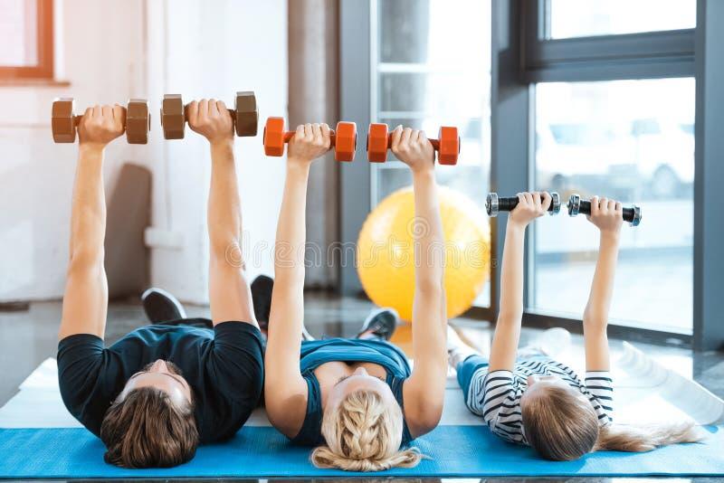 Rodzina ćwiczy z dumbbells przy sprawności fizycznej studiiem fotografia stock