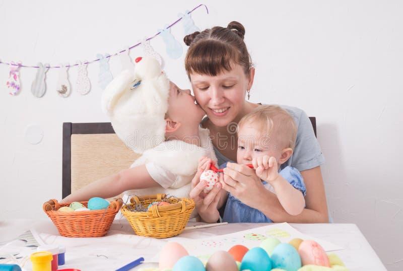 Rodzina świętuje Passover: Mama maluje wzór na Wielkanocnym jajku Syn całuje jego matki na policzku obraz stock