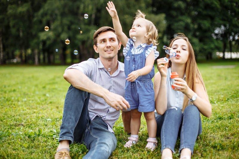 Rodzina bawić się z bąblami outdoors obrazy stock