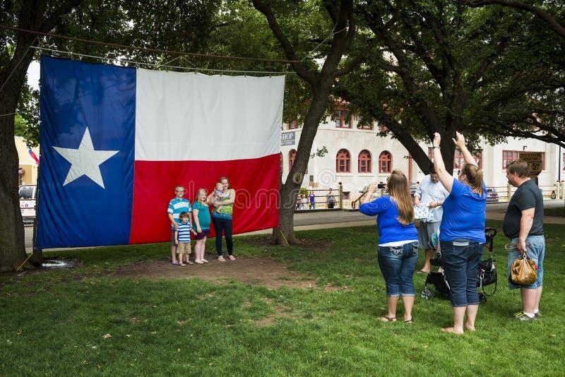 Rodzina bierze fotografię przed Teksas flaga Worth w Fort Worth Stockyards, Naprzód, Teksas fotografia royalty free