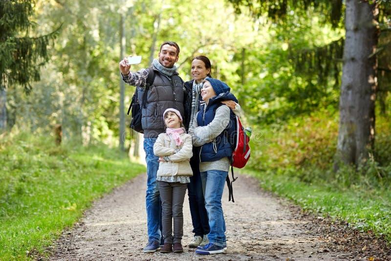 Rodzina bierze selfie z smartphone w drewnach zdjęcia royalty free
