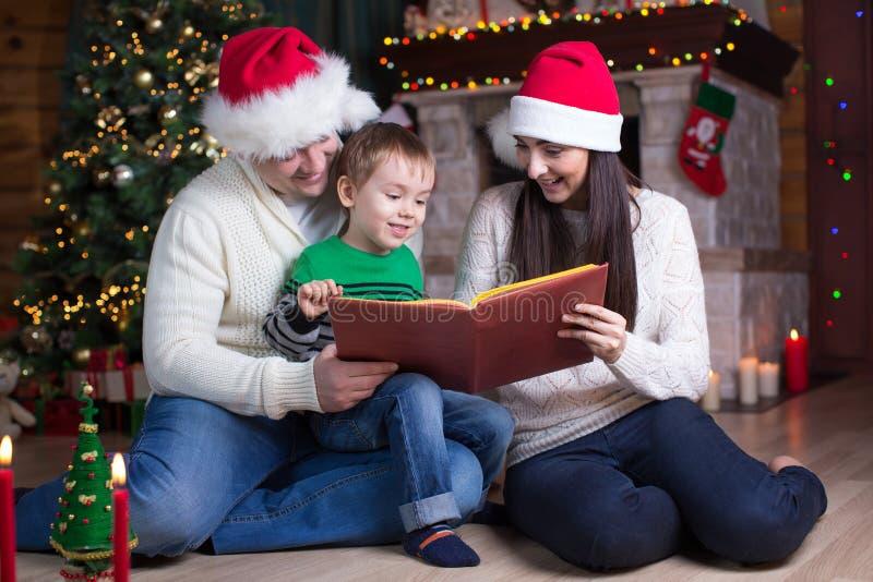Rodzina, boże narodzenia, mas, pojęcie - ono uśmiecha się rodzice w Santa synu i kapeluszach żartują czytelniczą książkę zdjęcia royalty free