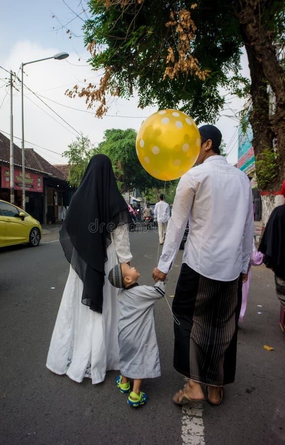 rodzina chodzi do domu po Eid modlitwy w alun-alun mieście Blitar, Wschodni Jawa, Indonezja zdjęcia royalty free