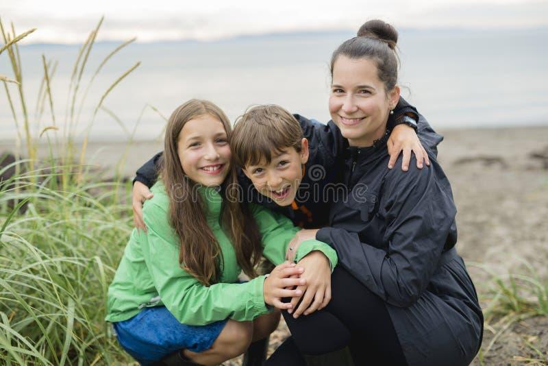 Rodzina cieszy się deszcz i ma zabawę outside na plaży szarość dżdżysta zdjęcie royalty free