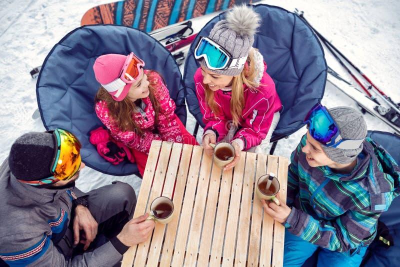 Rodzina cieszy się na gorącym napoju przy ośrodkiem narciarskim zdjęcia royalty free