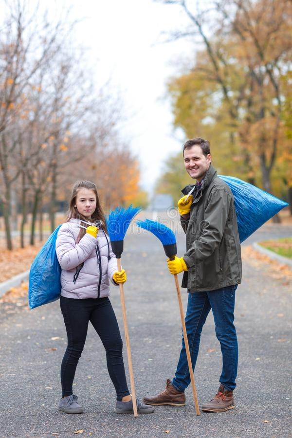 Rodzina, dziewczyna z tata czystym w jesień parku, stojak z torba na śmiecie i chwyt miotły, obraz stock
