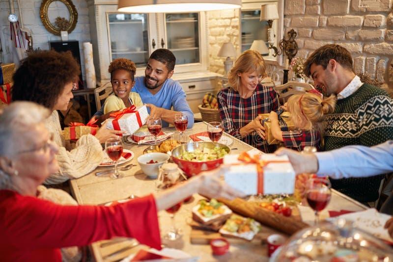 Rodzina i przyjaciele cieszymy się na Bożenarodzeniowym gościu restauracji i wymieniamy teraźniejszość wpólnie zdjęcie stock