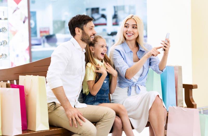 Rodzina Korzystająca Z Zniżek Wyszukiwania Telefonu Siedzących Na Stanowisku W Mall zdjęcie royalty free