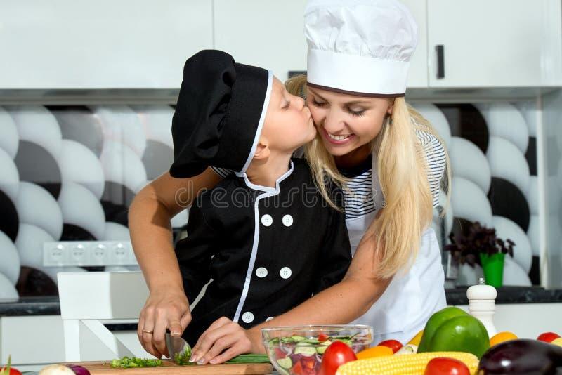 Rodzina kucharzi zdrowe jeść Matka i syn przygotowywamy jarzynowej sałatki w kuchni obrazy stock