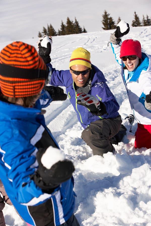 Rodzina Ma Snowball Walkę Na Narciarskim Wakacje fotografia stock