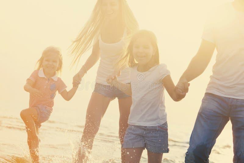 Rodzina ma zabawy runÑ 'ing na plaży przy zmierzchem zdjęcie royalty free