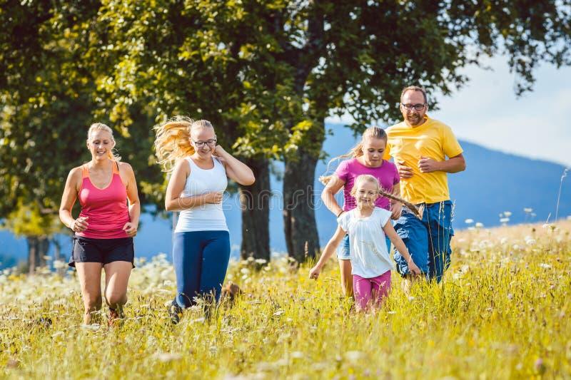 Rodzina, matka, ojciec i dzieciaki biega dla sporta, obraz royalty free