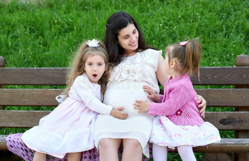 Rodzina na plenerowy, kobieta w ciąży z dzieckiem w miasto parku, zdziwionej dziewczyny otwarty usta i, mówi no! no!, lato sezon, obrazy stock