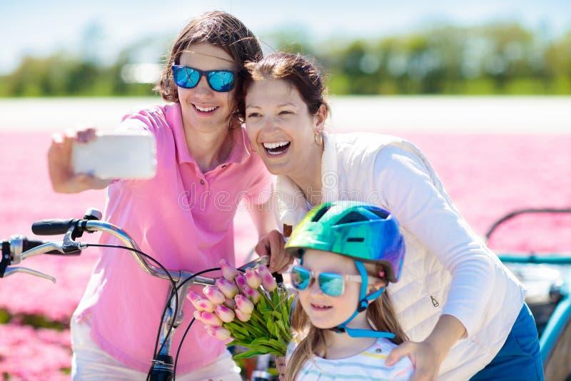 Rodzina na rowerze w tulipanowych kwiat?w polach, Holandia zdjęcie royalty free