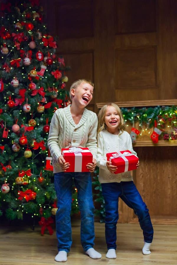 Rodzina na wigilii przy grabą Dzieciaki otwiera Xmas teraźniejszość obrazy stock