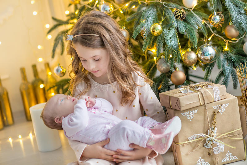 Rodzina na wigilii przy grabą Dzieciaki otwiera Xmas teraźniejszość Dzieci pod choinką z prezentów pudełkami Dekorujący utrzymani zdjęcia royalty free