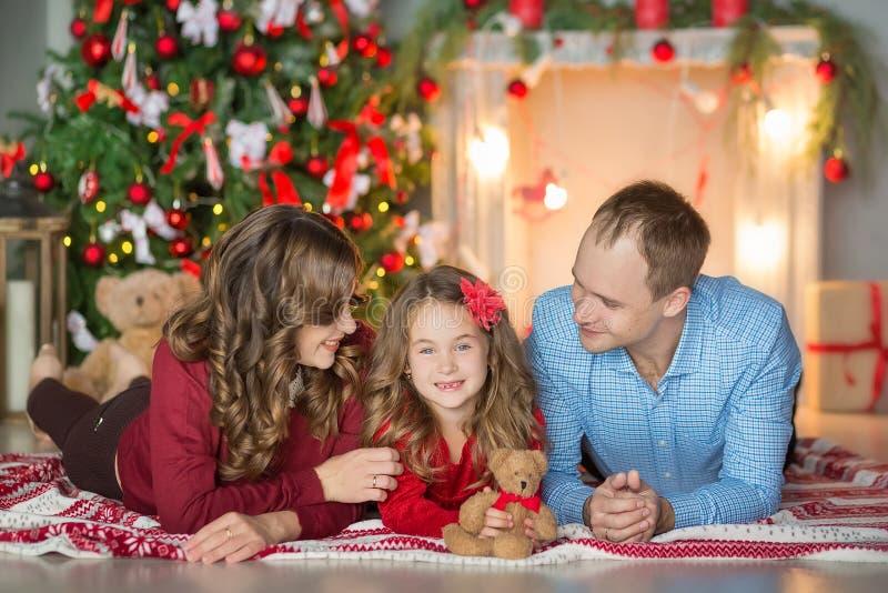 Rodzina na wigilii przy grabą Dzieciaki otwiera Xmas teraźniejszość Dzieci pod choinką z prezentów pudełkami Dekorujący utrzymani fotografia stock