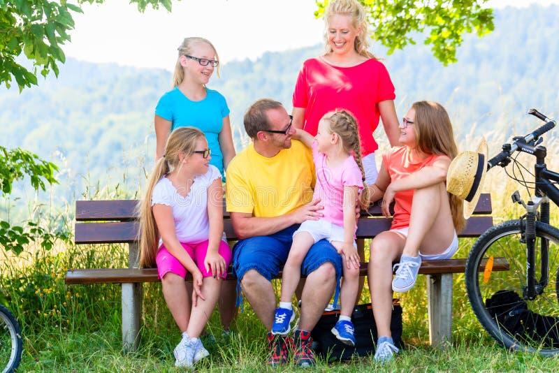 Rodzina na wycieczce turysycznej z rowerami ma odpoczynek na ławce zdjęcia stock