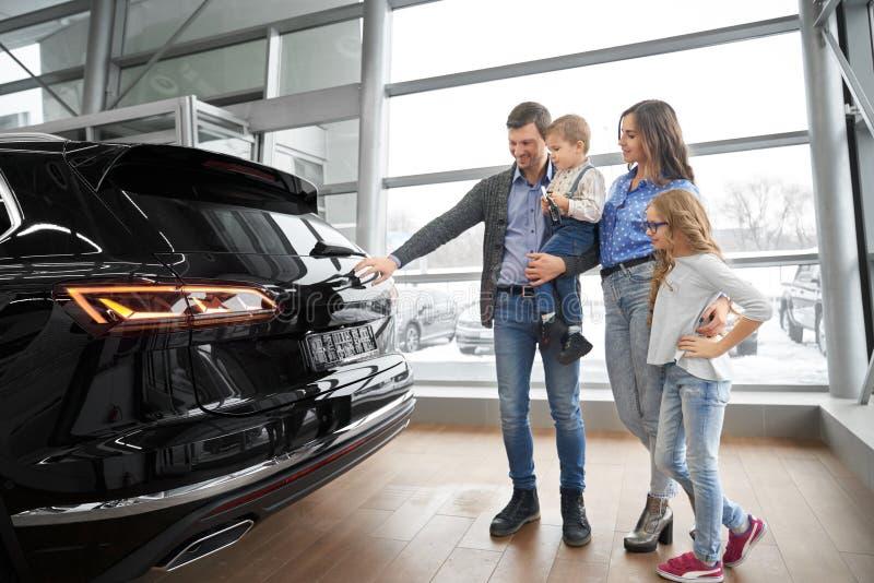 Rodzina obserwuje nowego czarnego samochód w sali wystawowej zdjęcia royalty free