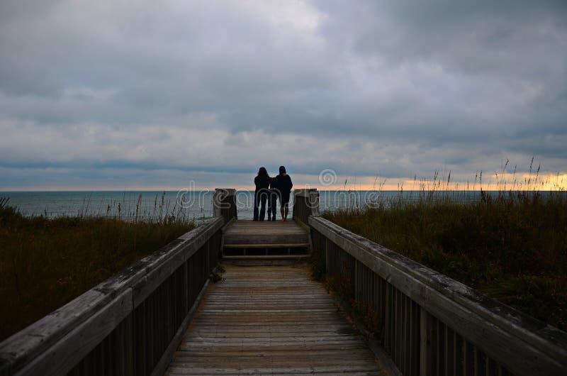 Rodzina ogląda wschód słońca przy plażą zdjęcie royalty free