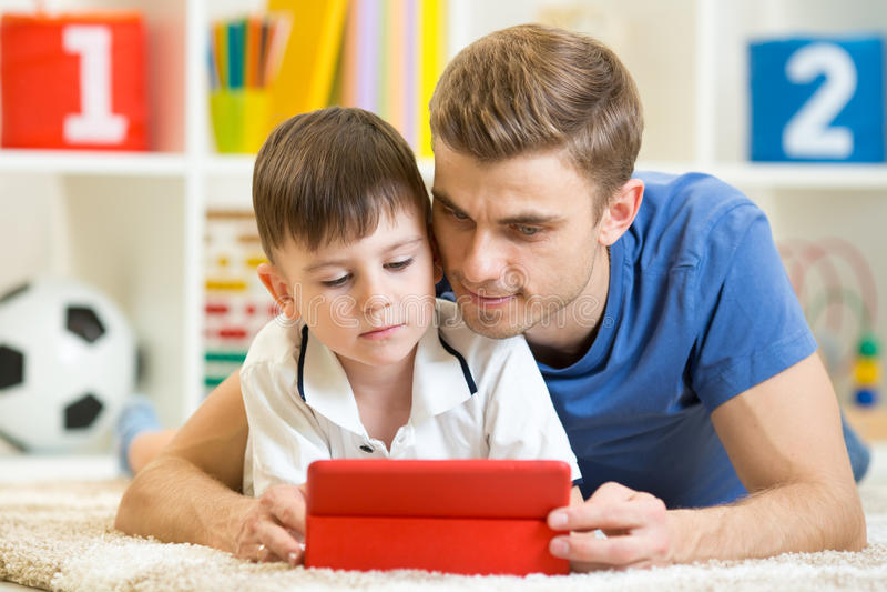 Rodzina - ojciec i syn z pastylka komputerem osobistym na podłoga przy obraz royalty free