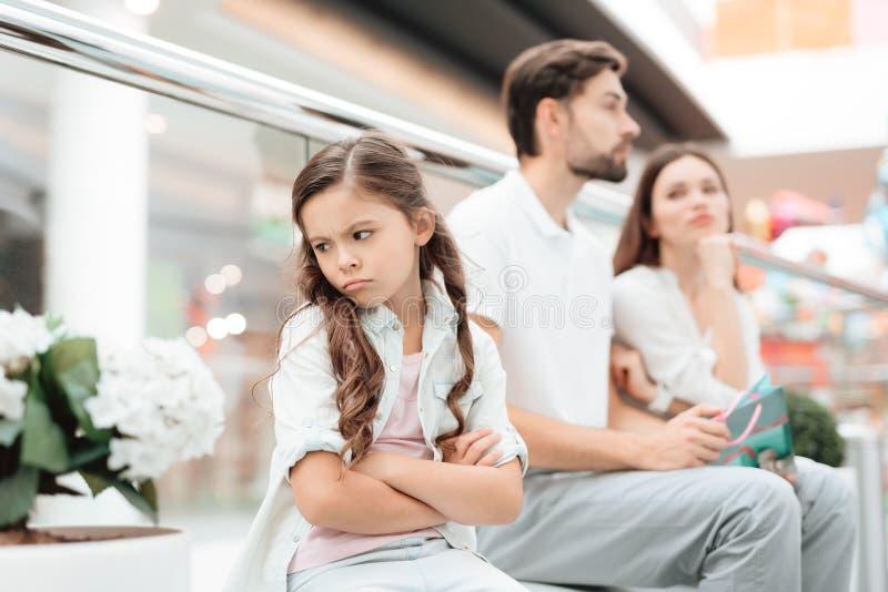 Rodzina, ojciec, matka i córka, siedzimy na ławce w centrum handlowym Dziewczyna jest gniewna i smutna zdjęcie stock