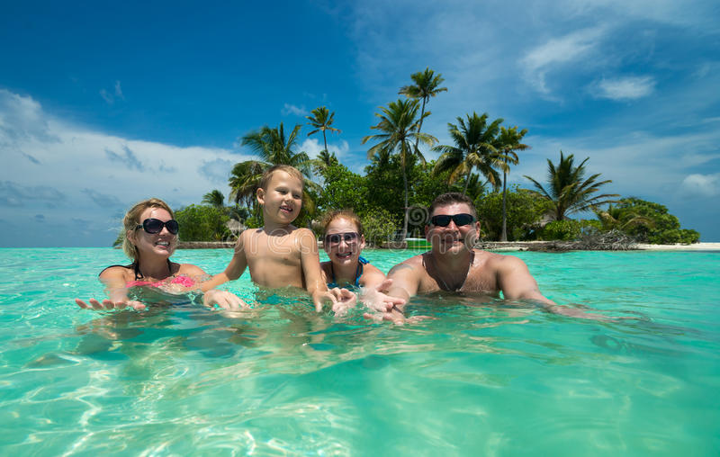 Rodzina pływa przeciw pięknej tropikalnej wyspie obraz royalty free