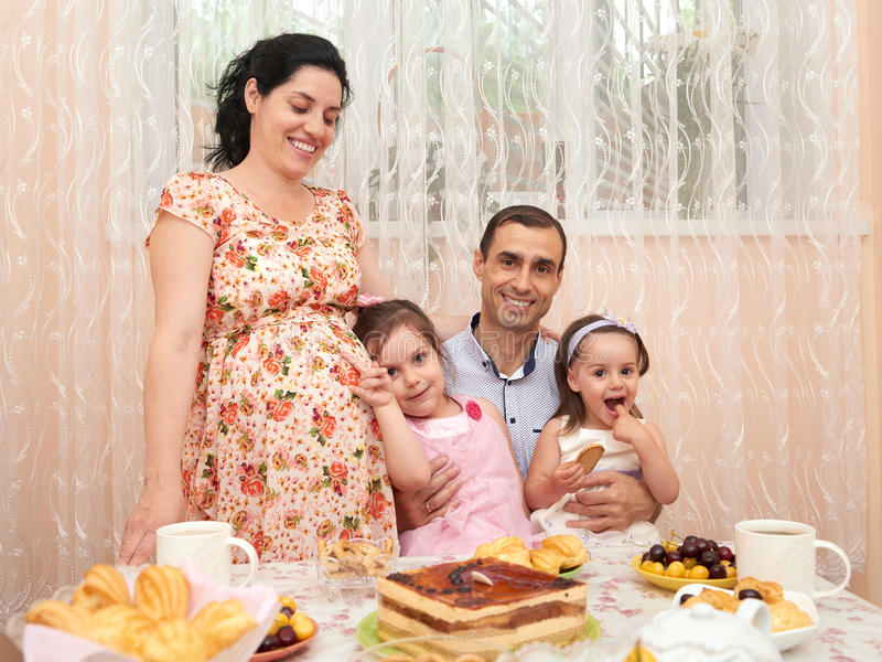 Rodzina pije herbaty w jadalni, kobieta w ciąży zdjęcia stock