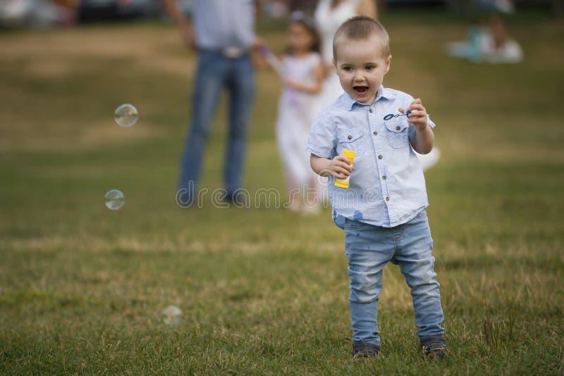 Rodzina podczas odprowadzenia w parku - chłopiec dmucha mydlanych bąble obrazy stock