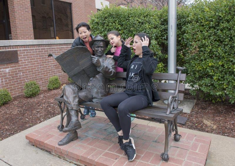 Rodzina pozuje humorously z brązem wola Rogers na ławce, Claremore, Oklahoma obrazy stock