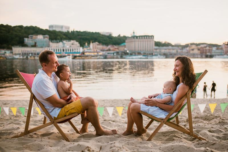 Rodzina przy nadmorski w wieczór na otwartym powietrzu kawiarni Matka, ojciec i dwa syna siedzimy na słońc loungers, patrzeje zmi obrazy stock