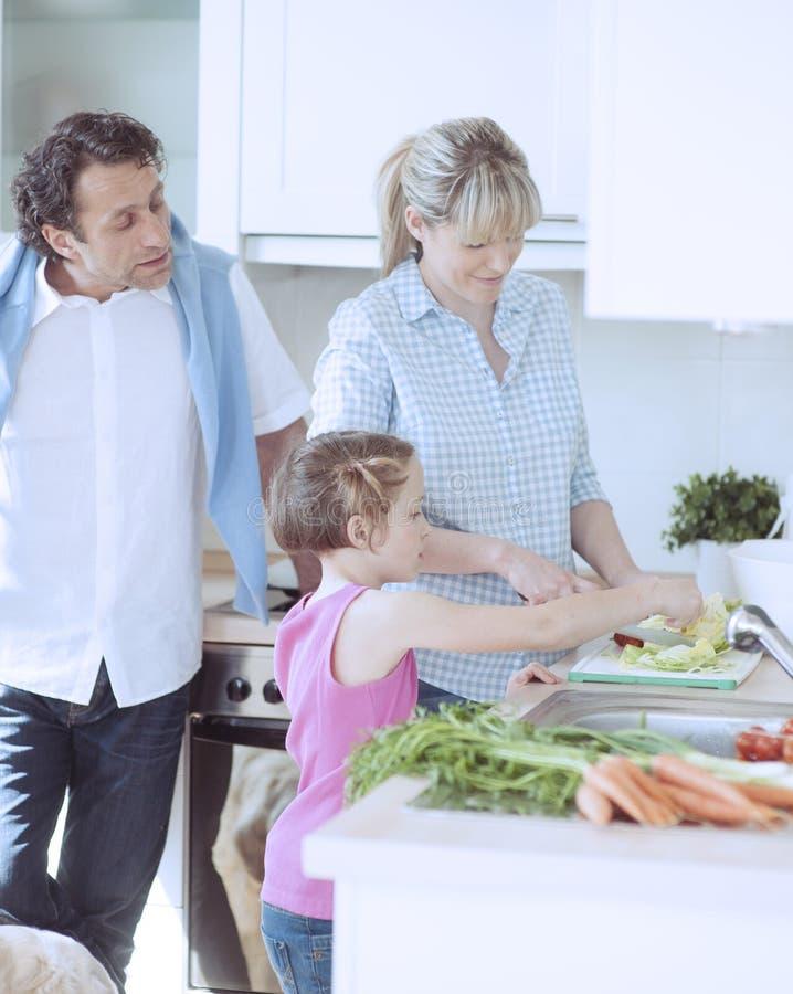 Rodzina robi zdrowej sałatki w kuchni zdjęcia stock