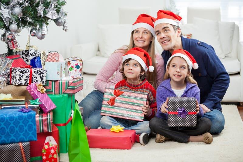 Rodzina Siedzi Bożenarodzeniowymi teraźniejszość W Santa kapeluszach zdjęcia royalty free