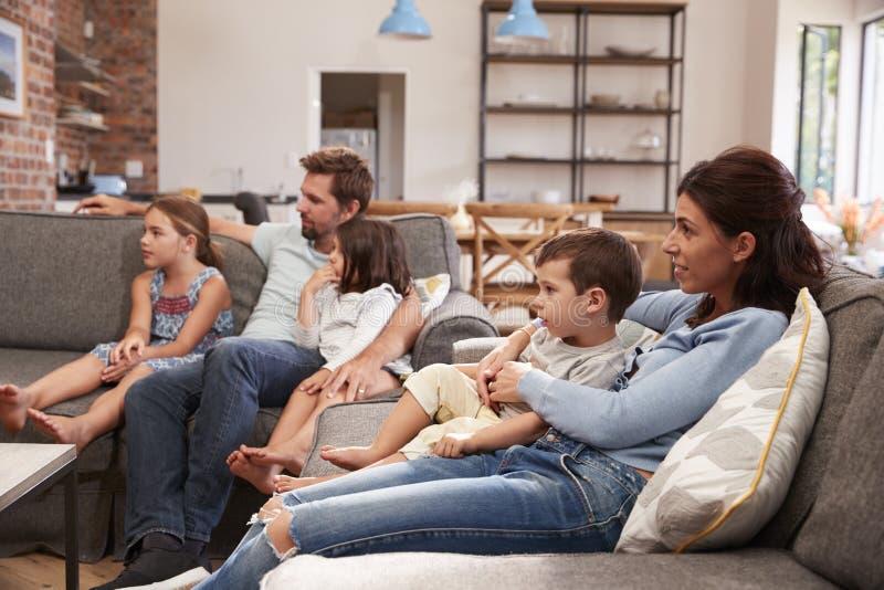 Rodzina Siedzi Na kanapie W Otwartej planu holu dopatrywania telewizi zdjęcia stock