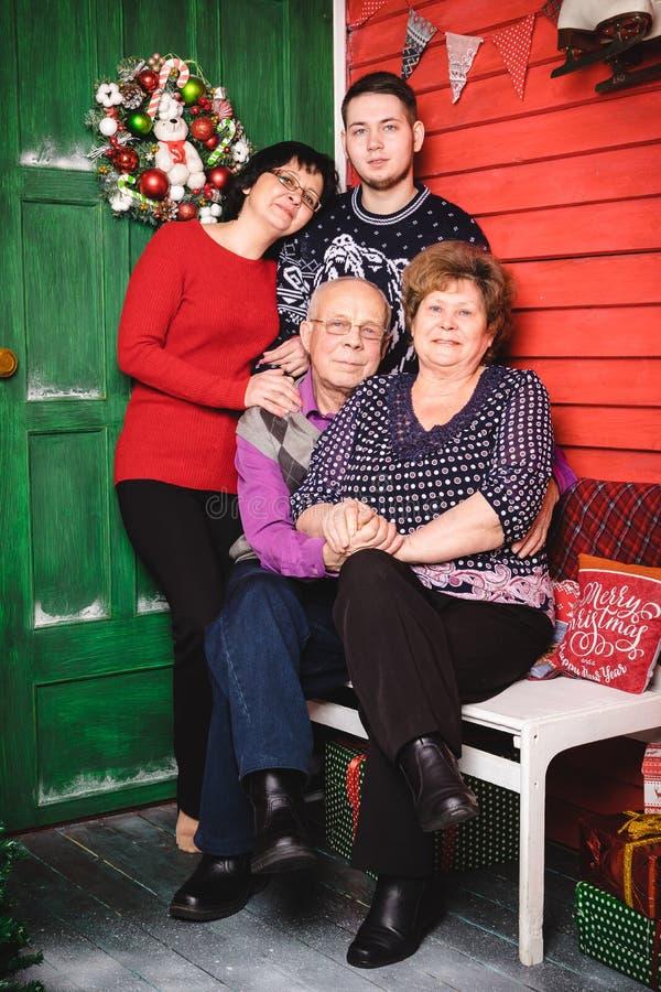 Rodzina składać się z matki, babcia, dziad, wnuk w pokoju dekorującym dla bożych narodzeń fotografia royalty free