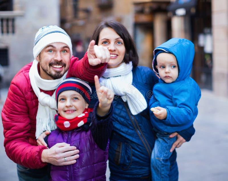 Rodzina składająca się z czterech osób chodzi w mieście i przyglądającym showplace obraz royalty free