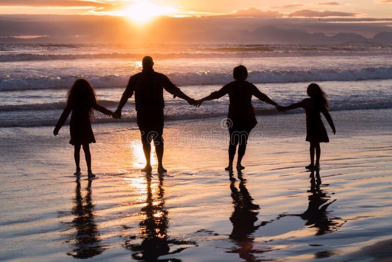 Rodzina składająca się z czterech osób trzyma ręk sylwetki fotografia royalty free