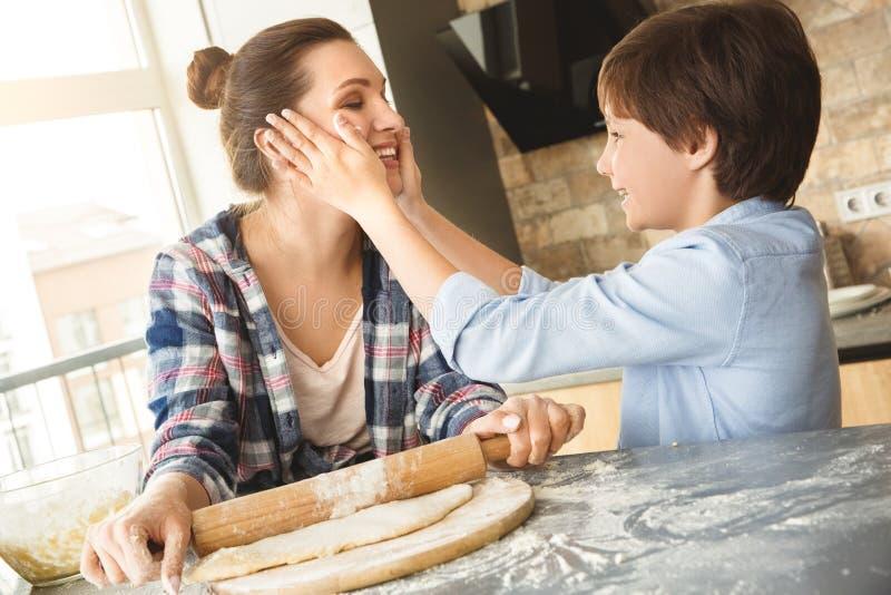 Rodzina stoi przy stołem w kuchnia syna mienia matki twarzy rozochoconej z floured rękami wpólnie w domu podczas gdy ona obrazy royalty free