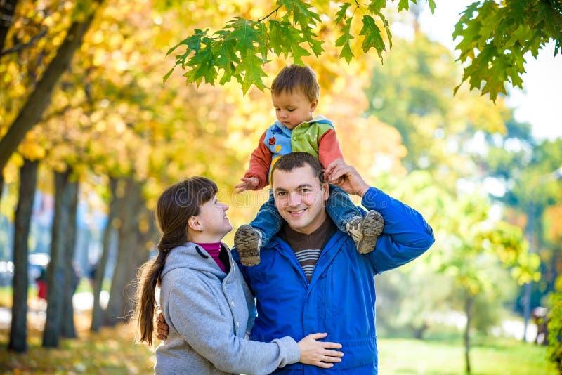 Rodzina trzy spaceru w jesień parka mienia rękach Szczęśliwy fa obrazy royalty free