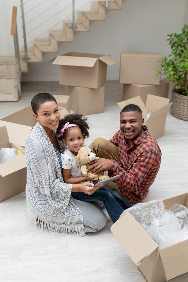 Rodzina używa cyfrową pastylkę w żywym pokoju podczas gdy odpakowywający karton w domu zdjęcia stock