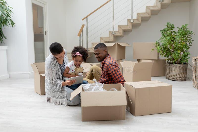 Rodzina używa cyfrową pastylkę w żywym pokoju podczas gdy odpakowywający karton obrazy stock