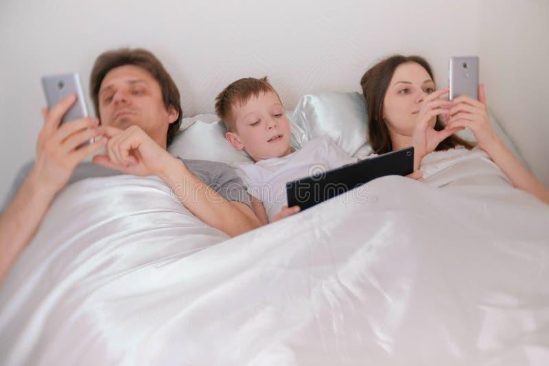Rodzina używa urządzenie przenośne telefony i pastylki lying on the beach w łóżku w ranku obraz stock