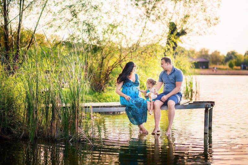 Rodzina w lecie na pinkinie blisko stawu, woda Rodzinny wakacje w naturze Troszkę córka z jej ojcem i ciężarnym mothe fotografia stock