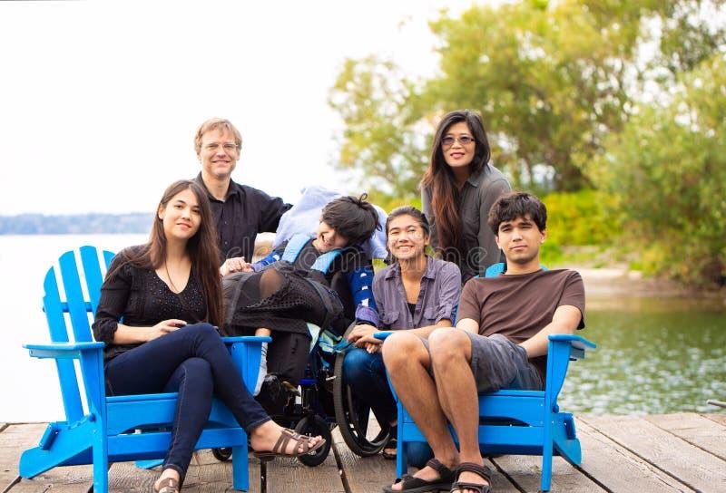 Rodzina z dodatkiem specjalnym potrzebuje dziecka siedzi outdoors wpólnie w sumie obraz royalty free