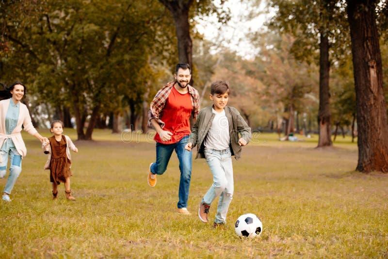 Rodzina z dwa dziećmi biega piłkę nożną w wpólnie i bawić się zdjęcie stock