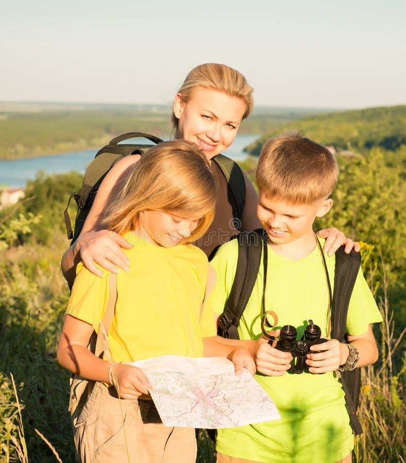 Rodzina z dwa dzieciakami patrzeje mapę, rodzinna podróż Matka i c obraz stock