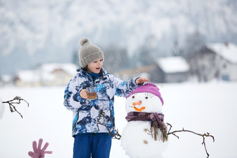 Rodzina z dziećmi, buduje bałwanu w parku w małym vil fotografia royalty free