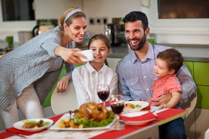 Rodzina z dziećmi robi Bożenarodzeniowemu selfie przy ustawiającym stołem zdjęcie stock