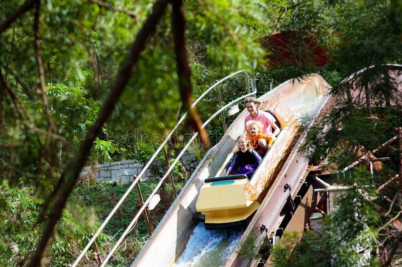Rodzina z dzieciakami na kolejce górskiej w rozrywkowym parku tematycznym Dzieci jedzie wysokiego prędkości wodnego obruszenia pr zdjęcie royalty free